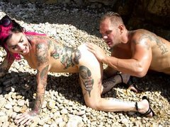 tattooed couple having fun on the beach